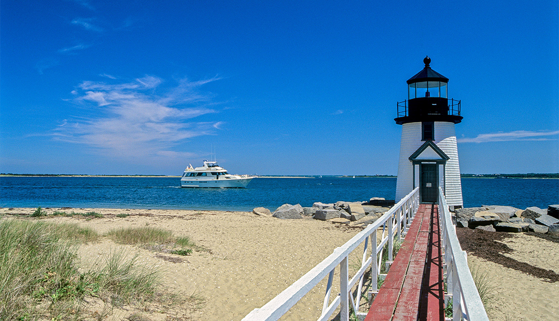 item 8 of Gallery image - Brant Point Light and cabin cruiser yacht in Nantucket