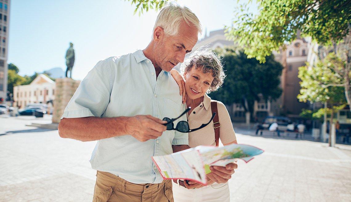 Pareja de adultos mayores observan un mapa mientras están en la calle.