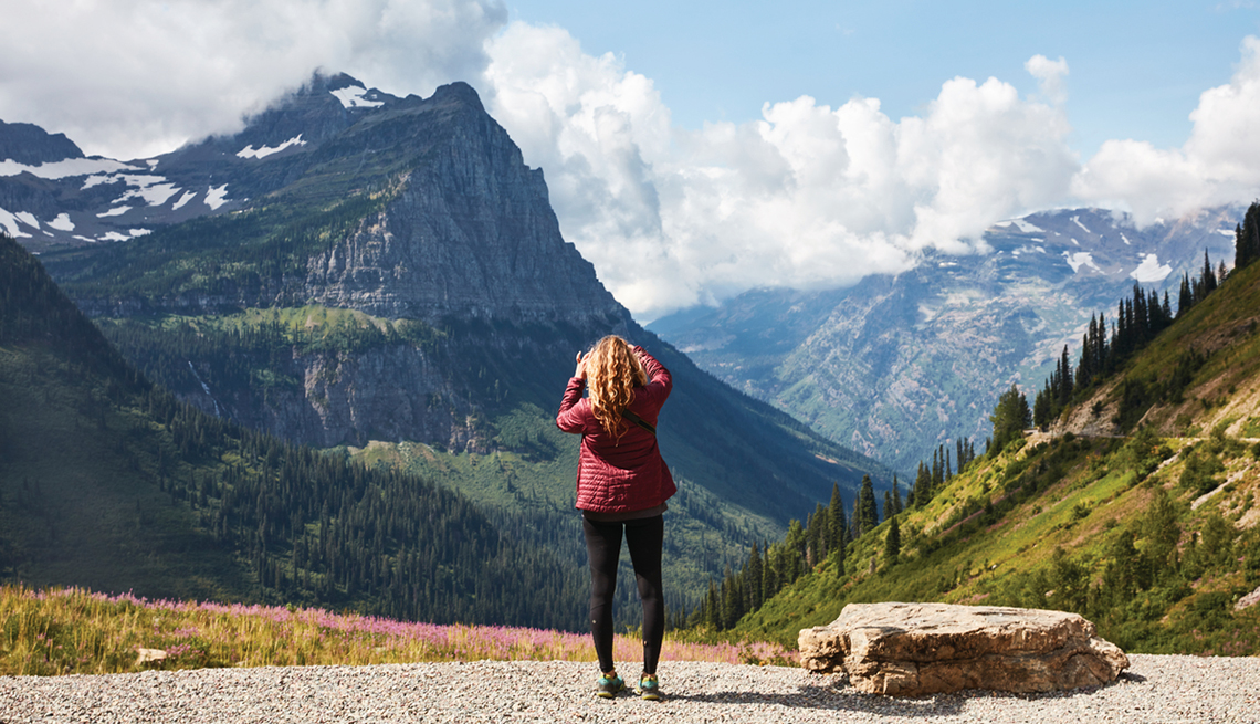 woman taking a photo of snow-capped mountains in Glacier National Park