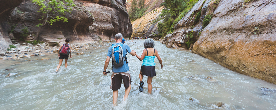 A senior couple, holding hands, wades through a beautiful red slot canyon in Utah. The walls are rising up high on both sides above and around them.There is a hiker a short ways ahead of them as they hold hands and trek through the water.