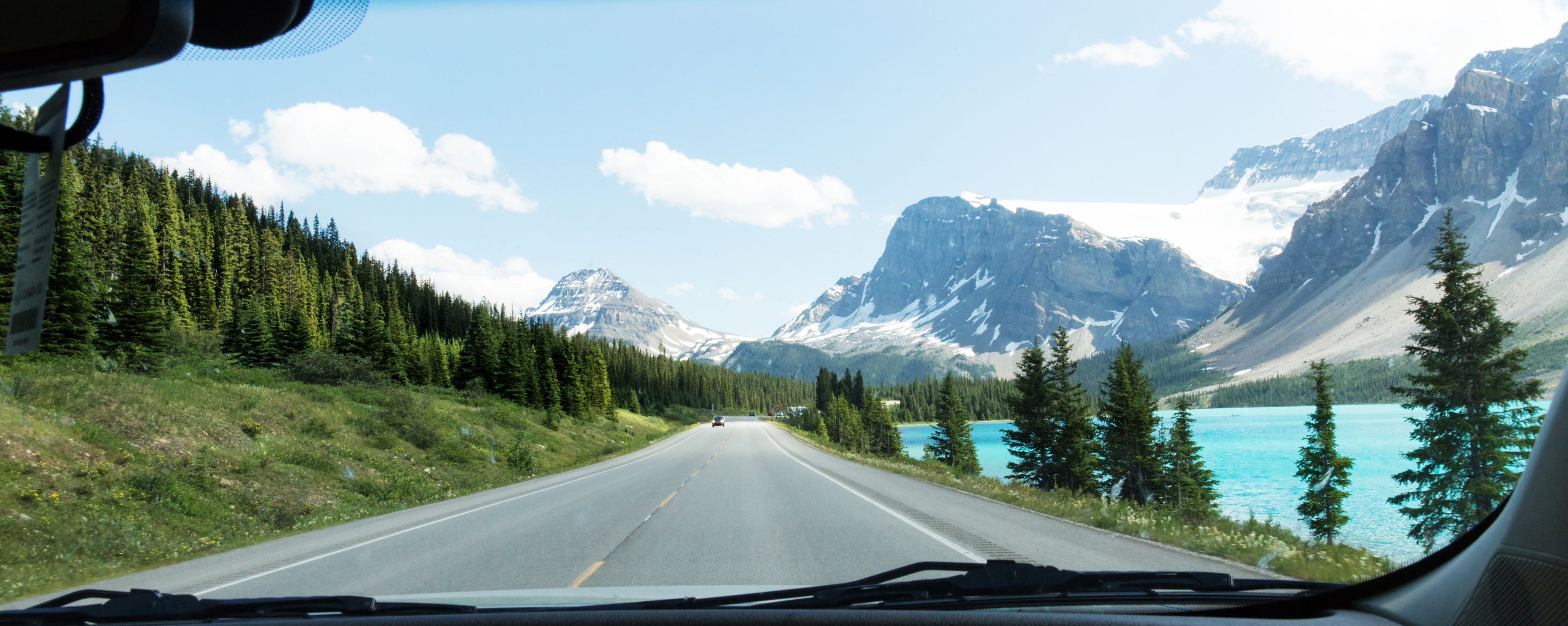 shot taken from inside a car looking out windshield while driving on a beautiful mountain lake road