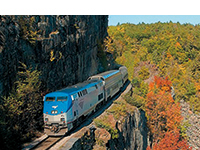 an amtrak great dome car train skirts the shore of Lake Champlain along the tracks surrounded my a high cliff wall and fall foliage.