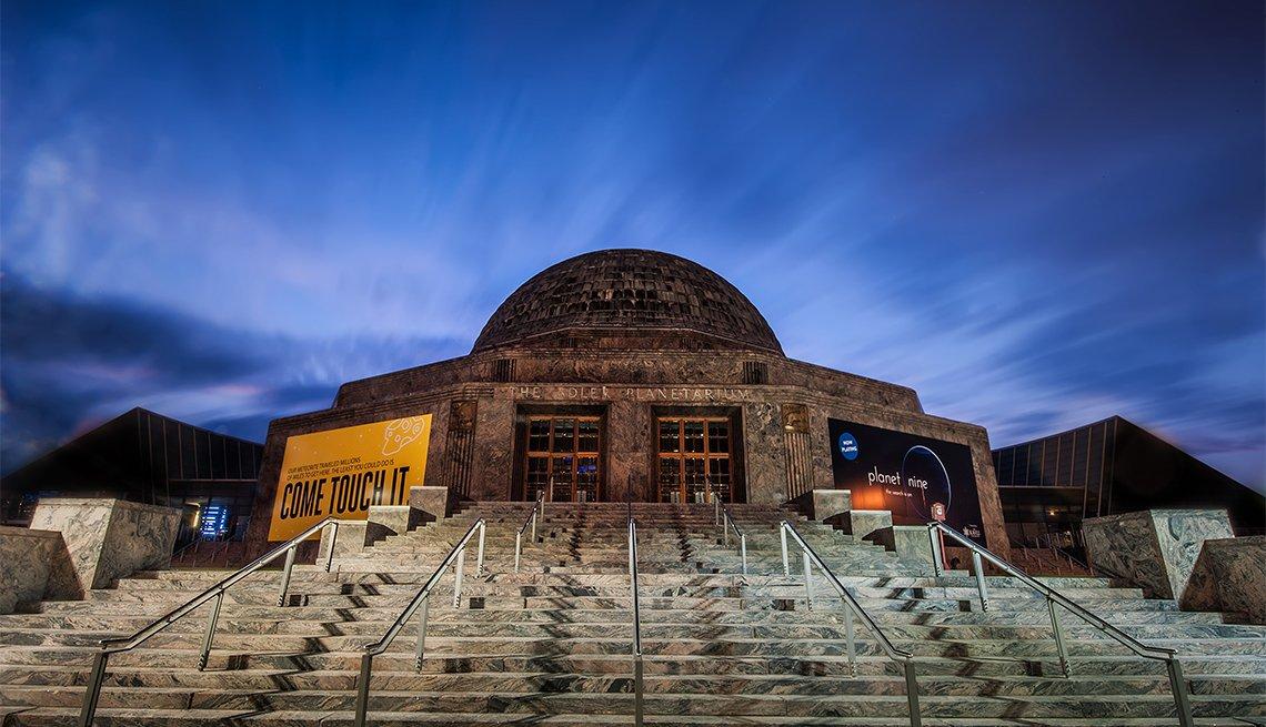 sun rising behind the Adler Planetarium