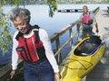 Pareja de adultos mayores llevando un kayak a pie en un muelle