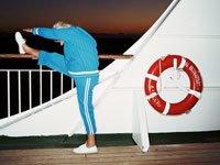 Mujer mayor hace ejercicios de estiramiento en la barandilla de un buque