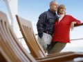 Mature couple lean against cruise ship railing, Frommers:  How Not to Overspend On A Cruise