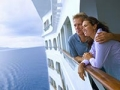 Couple leaning on rail of cruise ship, looking at ocean (Getty Images)