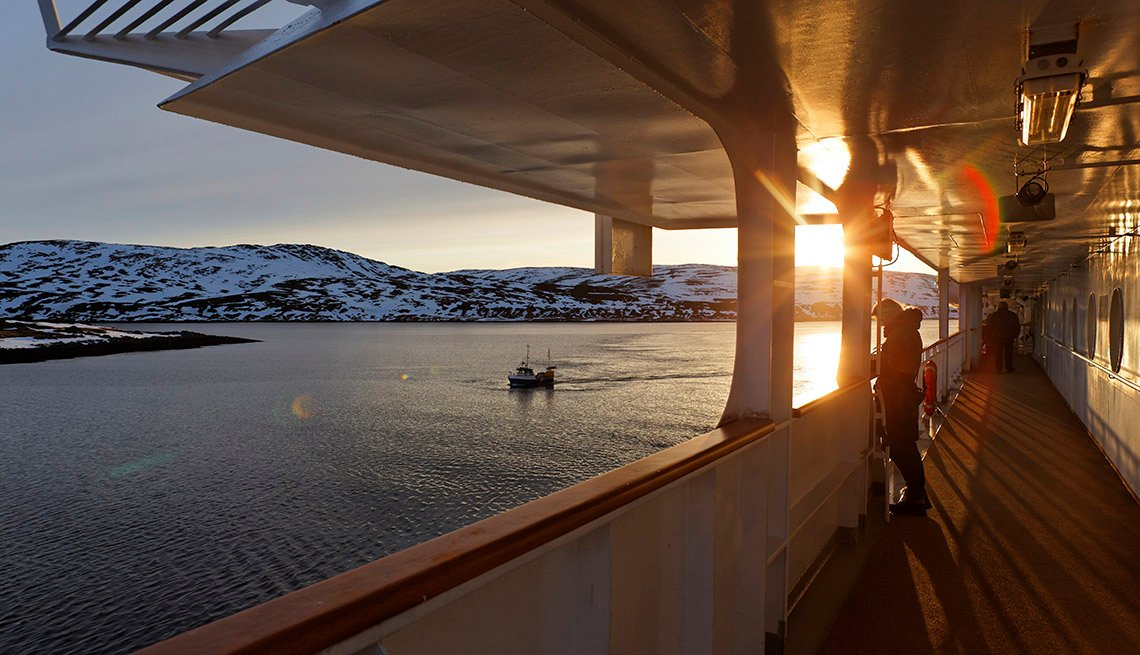 Passenger Enjoys The Sunset On The Deck Of A Cruise Ship With Snowy Mountains For A View, Unusual Cruise Destinations
