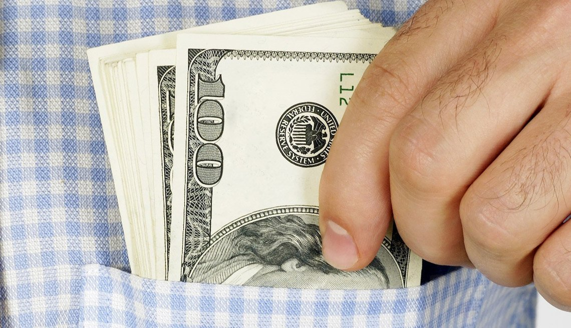 Close Up Of A Man's Hands Putting Wads Of 100 US Dollar Bills In His Shirt Pocket, How To Avoid Hidden Costs On Cruises