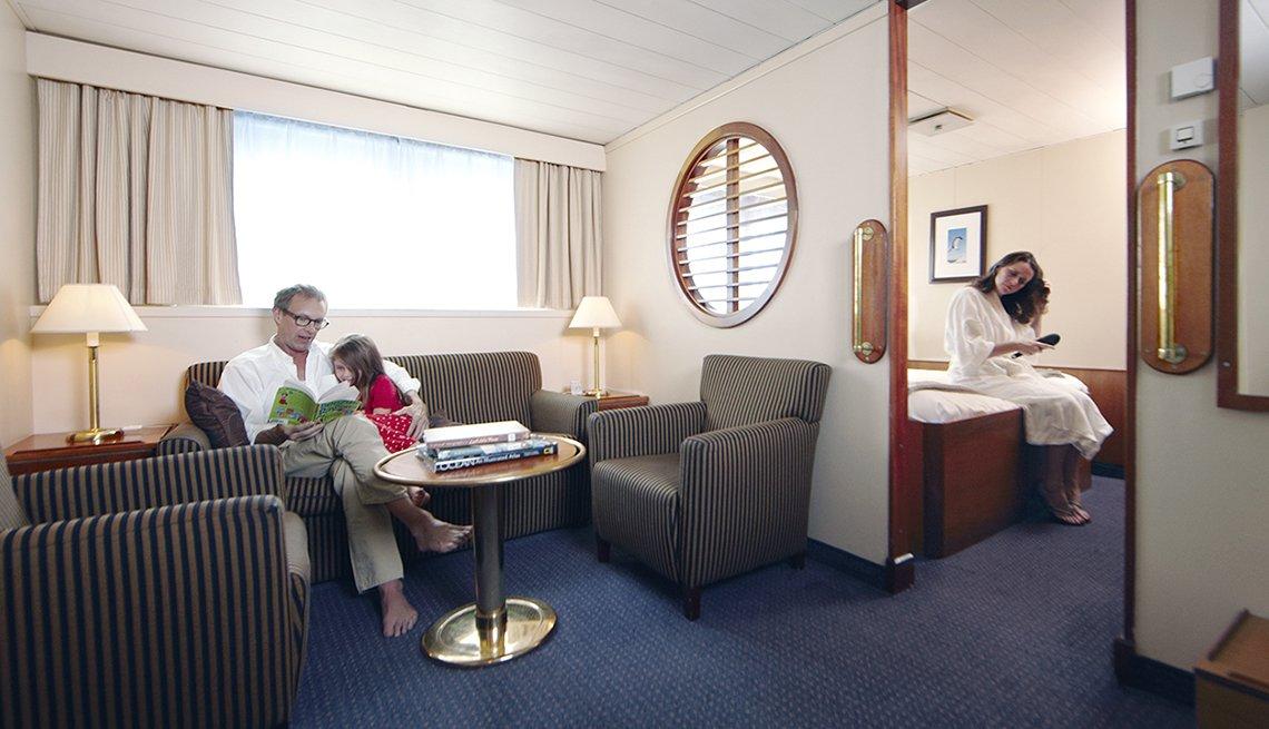 Padre lee un libro a su hija mientras que la madre se cepilla el pelo en la cabina de un crucero.