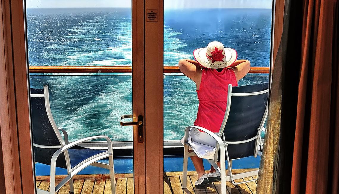 Mujer mira hacia el mar, mientras está sentada en el balcón de un crucero.