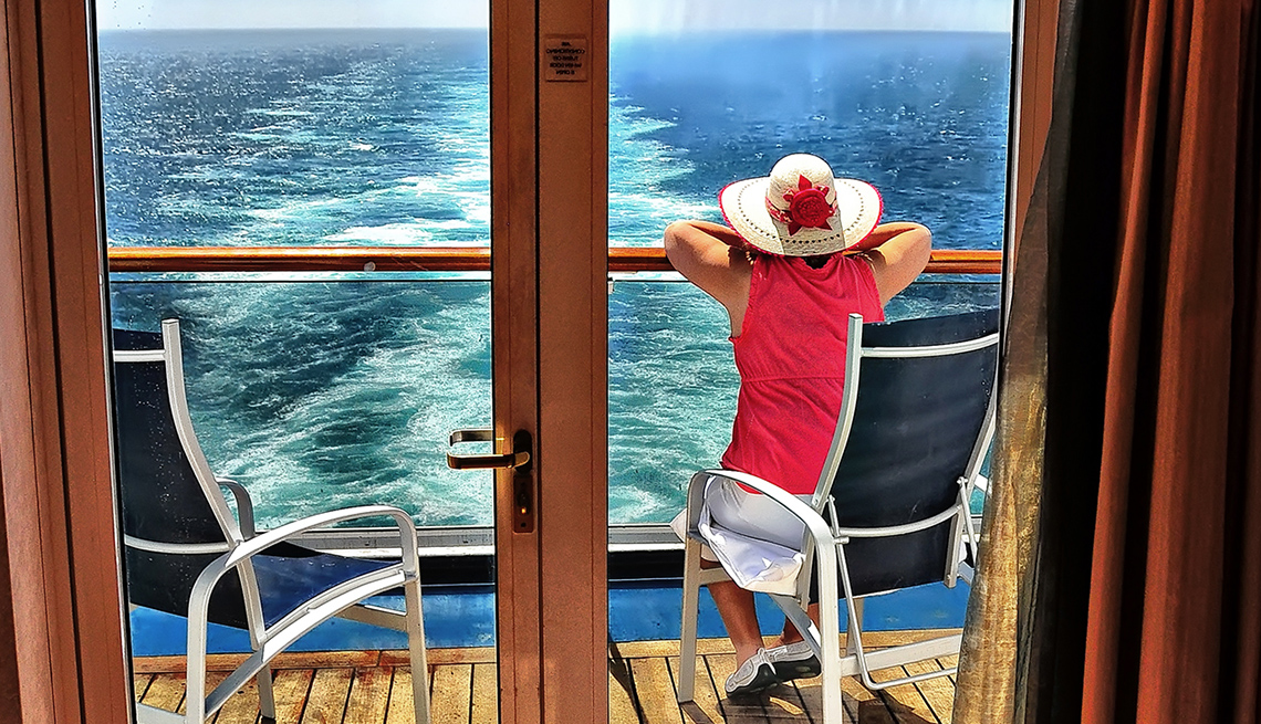 Woman in red dress sits on a chair on private balcony on cruise ship.