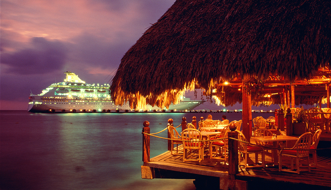 The lights of a cruise ship beyond a tiki bar on a pier over the ocean at night