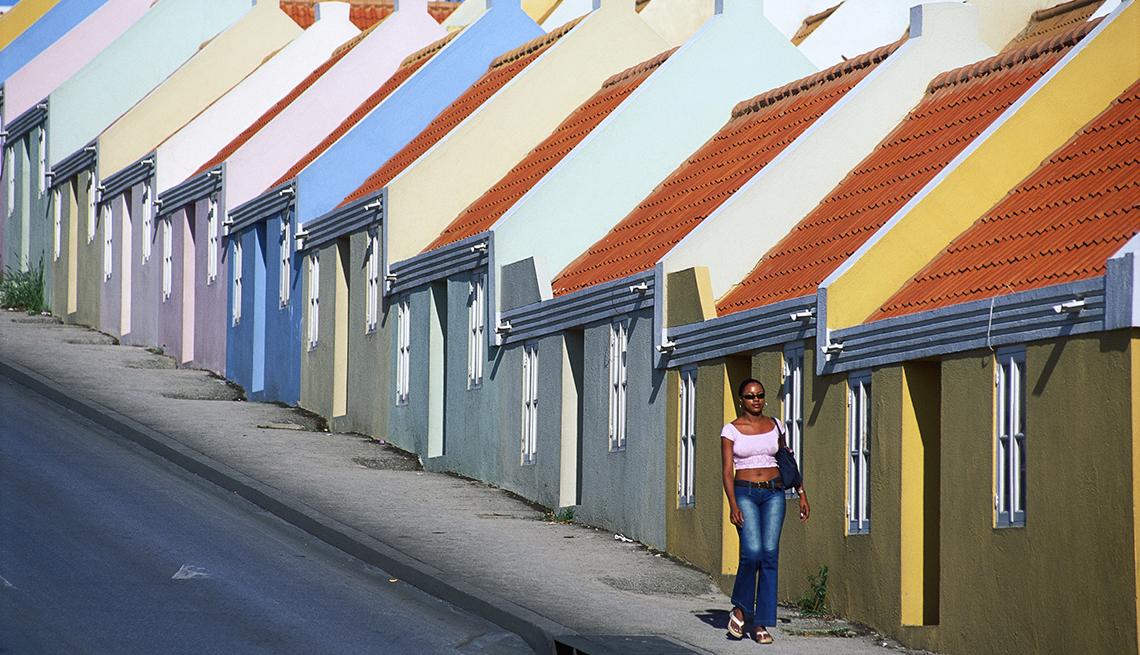 Mujer camina por la acera de una carretera con edificios pastel