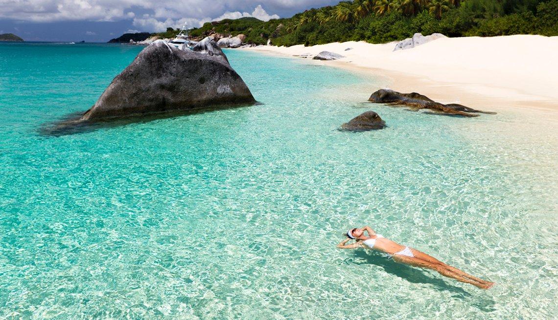 Mujer flotando en agua clara cerca de rocas y playa de arena blanca con palmeras