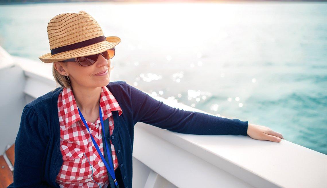 Una mujer observa el mar desde la cubierta de un crucero.