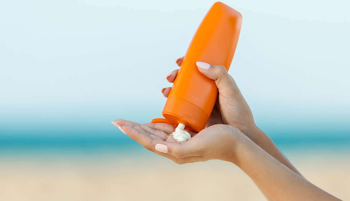 Mano de una mujer aplica protector solar en la playa.
