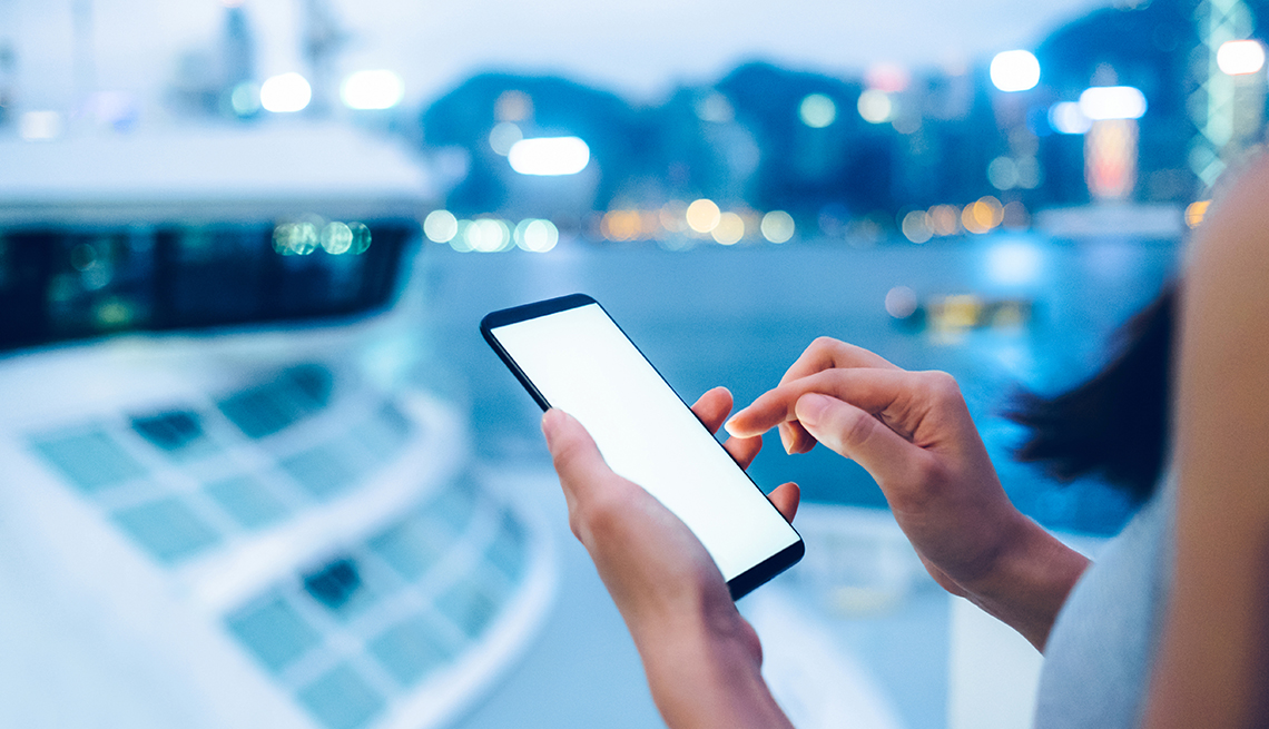woman on smartphone next to a cruise ship