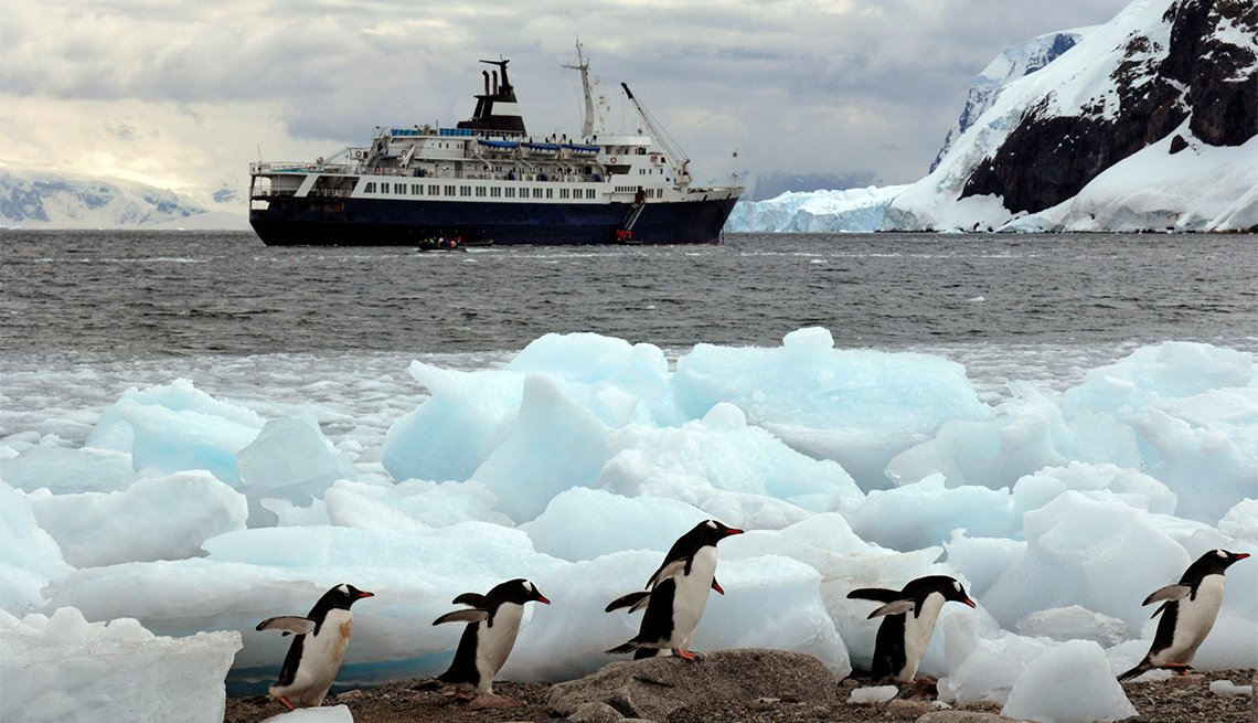A cruise ship in Niko Harbour off the coast of Antarctica - tourists in zodiac boats coming ashore and Penguins running through the ice