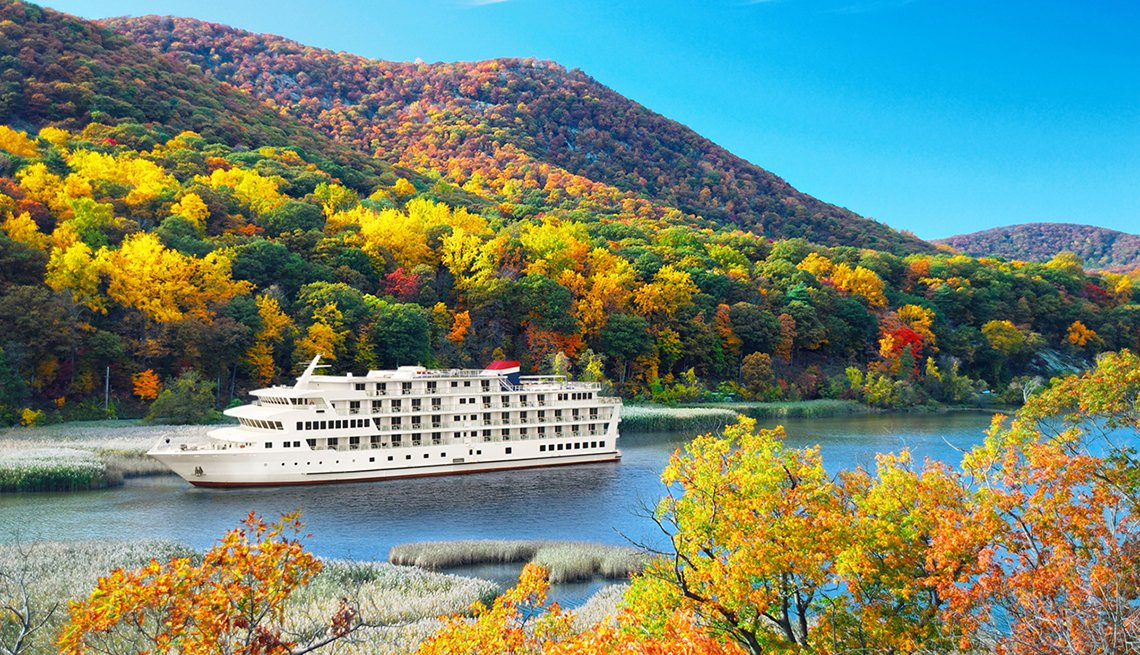 cruise ship sailing on a large river surrounded by hills of fall foliage