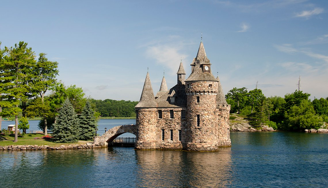 a castle standing at the end of a causeway in a river