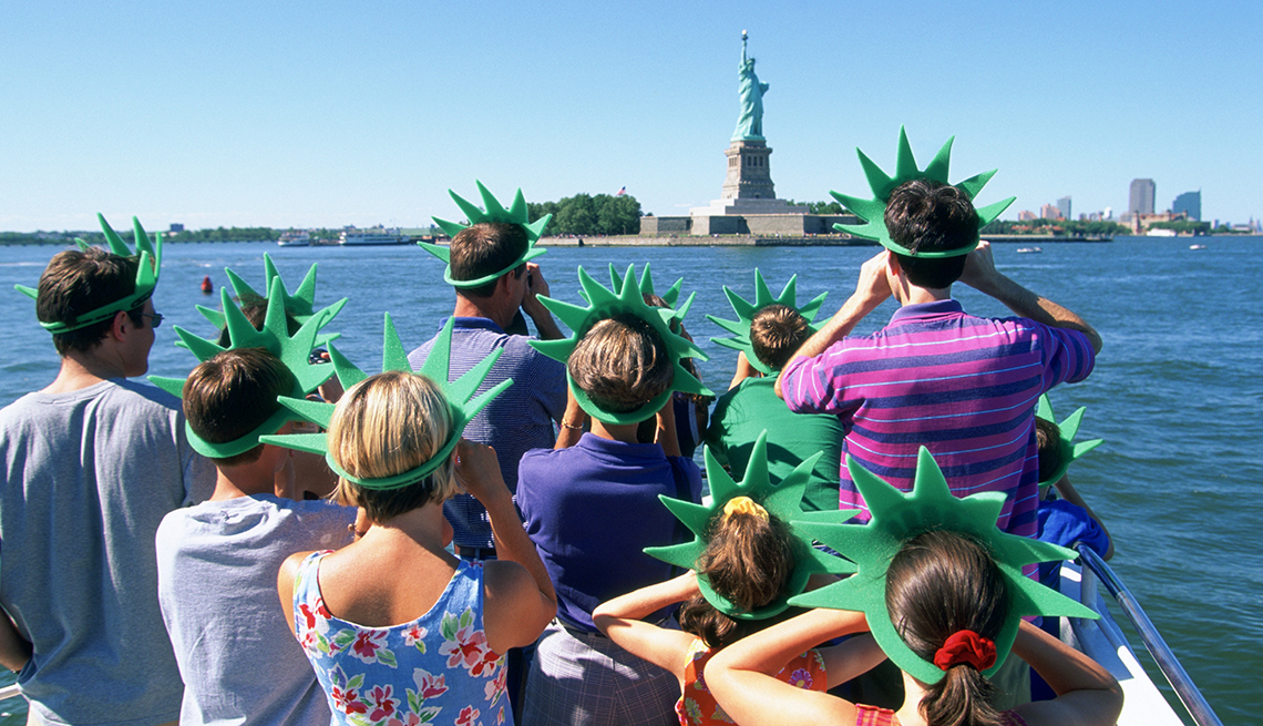 item 7 of Gallery image - A tour group on a boat looking at the statue of liberty.