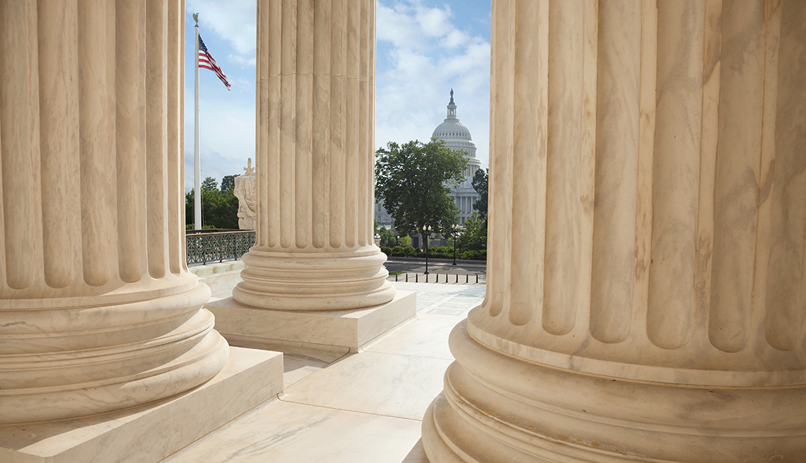 item 7 of Gallery image - Columns of the Supreme Court building with an American flag and the US Capitol in the background