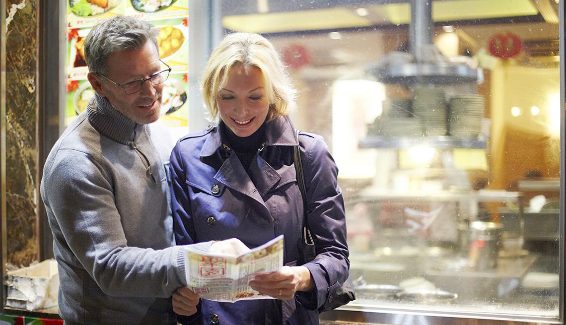 Couple reading menu at food cart, New York