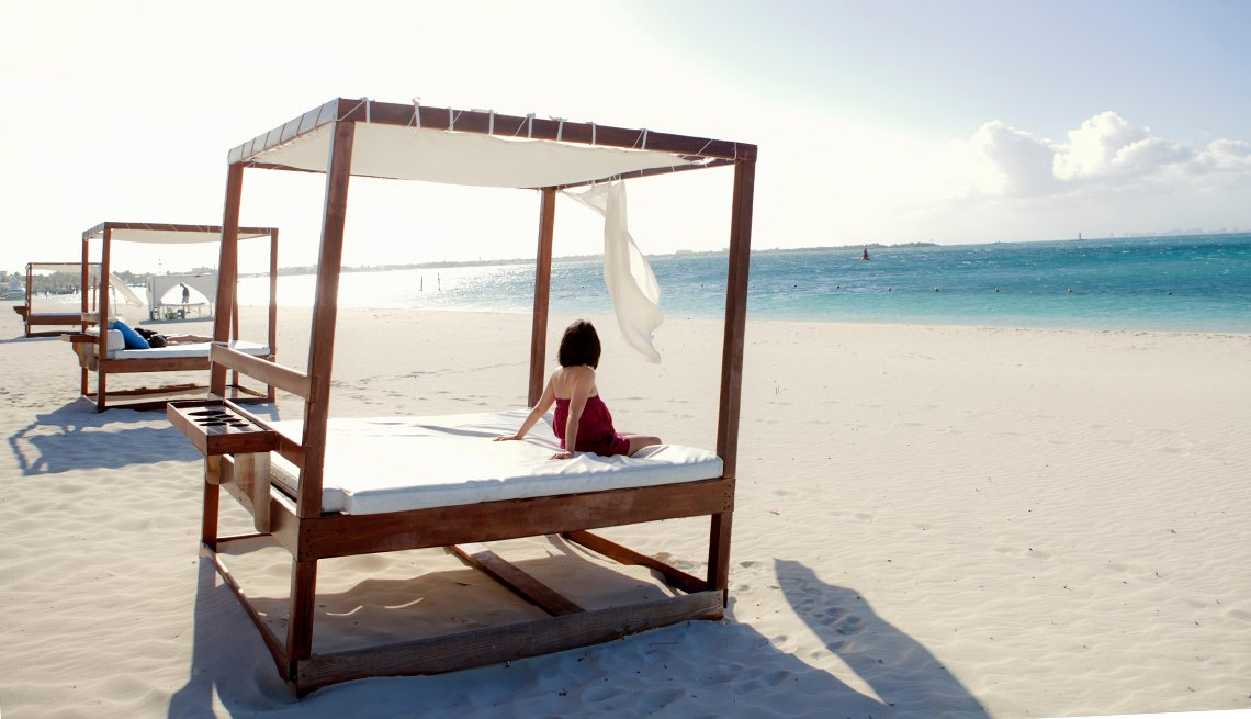 Woman sits on a bead on a beach in Cancun