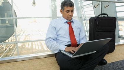 Hombre mayor trabajando en su computador portátil en un aeropuerto