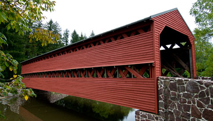 Covered bridge over a calm stream in Pennsylvania Heartland