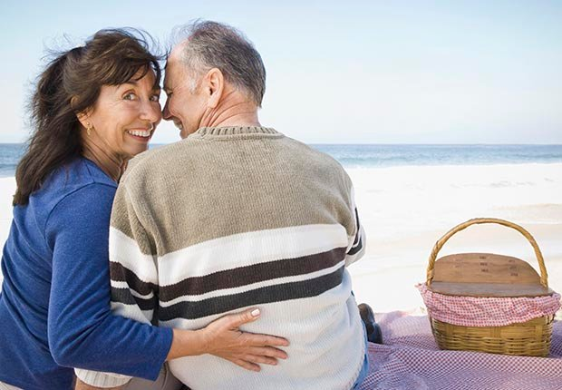 Couple having picnic on beach, Tips for Planning a Second Honeymoon (Corbis)