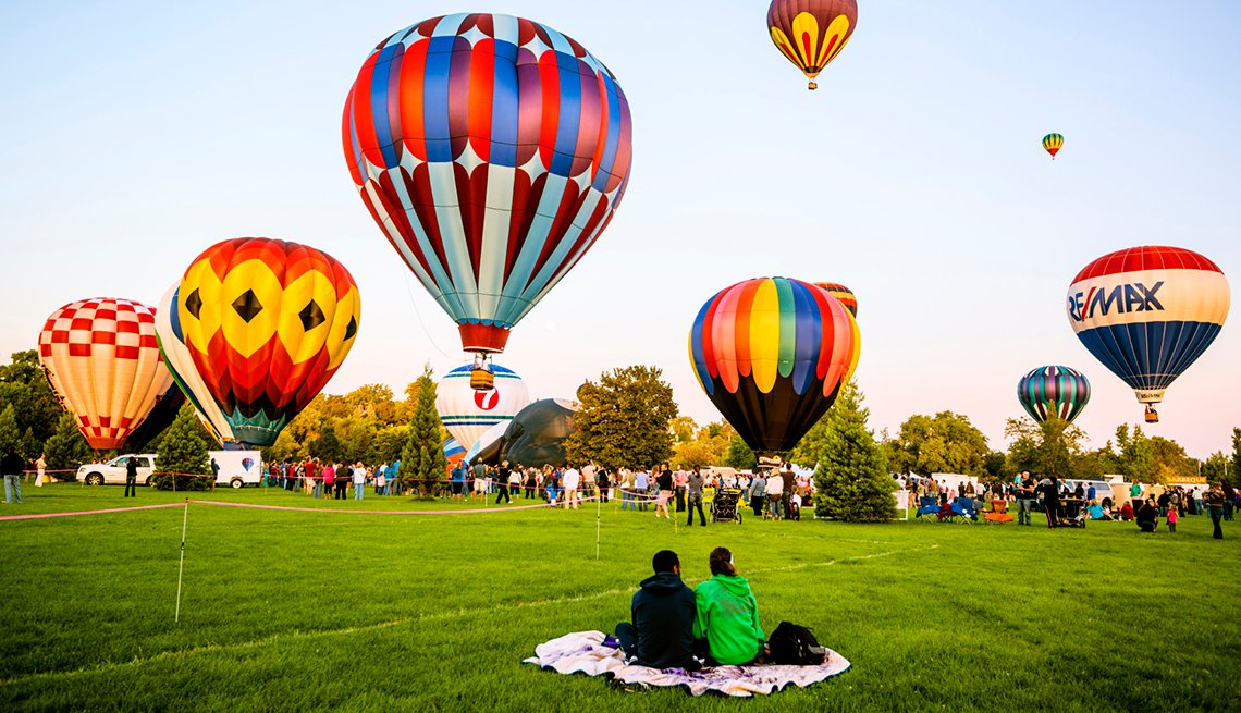 Couple on blanket watches hot air balloons, cities for outdoor fun