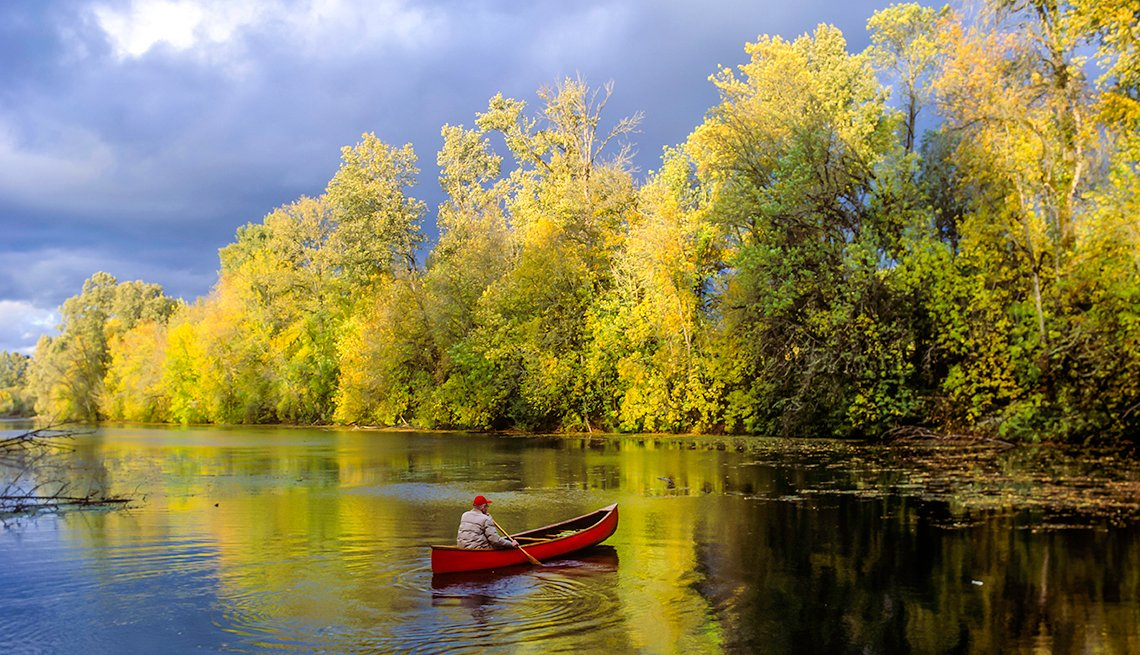 Person in red canoe on Willamette River, cities for outdoor adventure