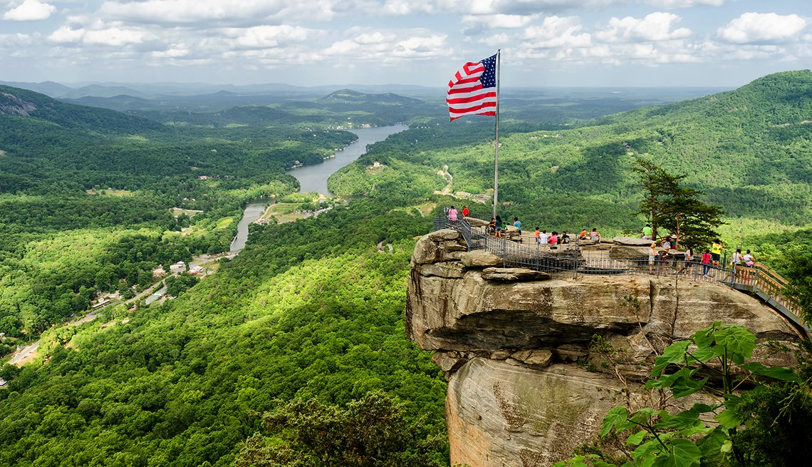 American flag and tourists view from Chimney Rock mountain, cities for outdoor fun