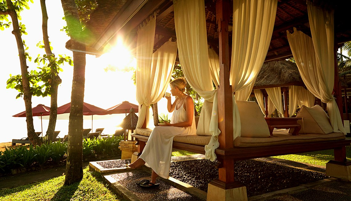 Woman relaxing in a cabana on a beach, affordable winter vacations