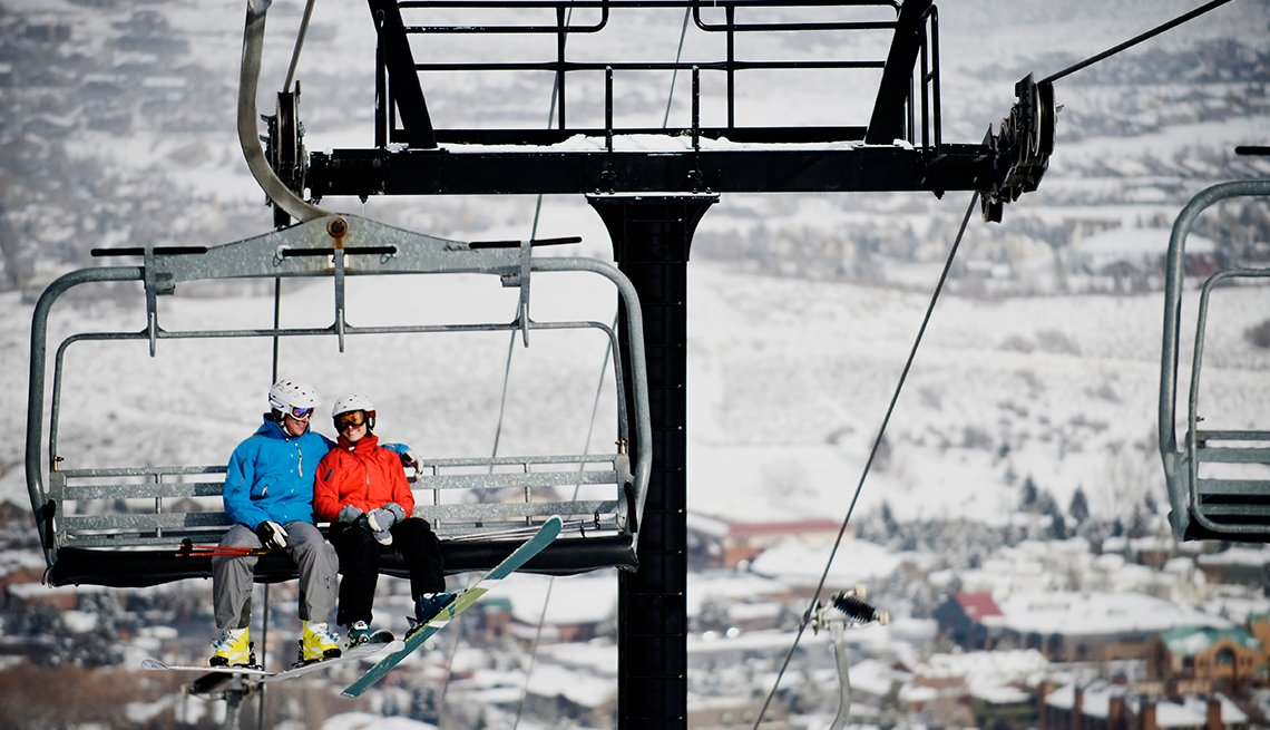 skiers ride a lift up a snow-covered mountain, affordable winter vacations