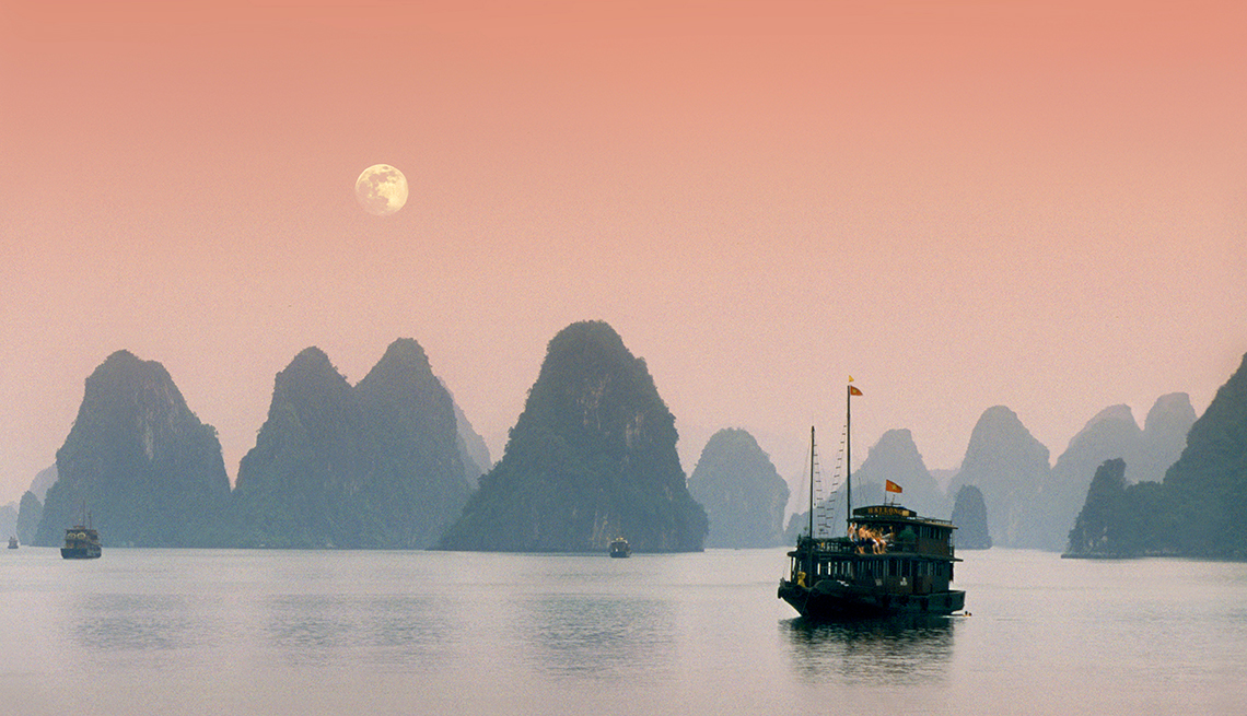 View of boat in Halong Bay in Vietnam and hills, affordable winter vacations