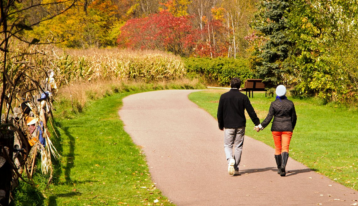 Couple holding hands walking down path near cornfield, cities for outdoor fun