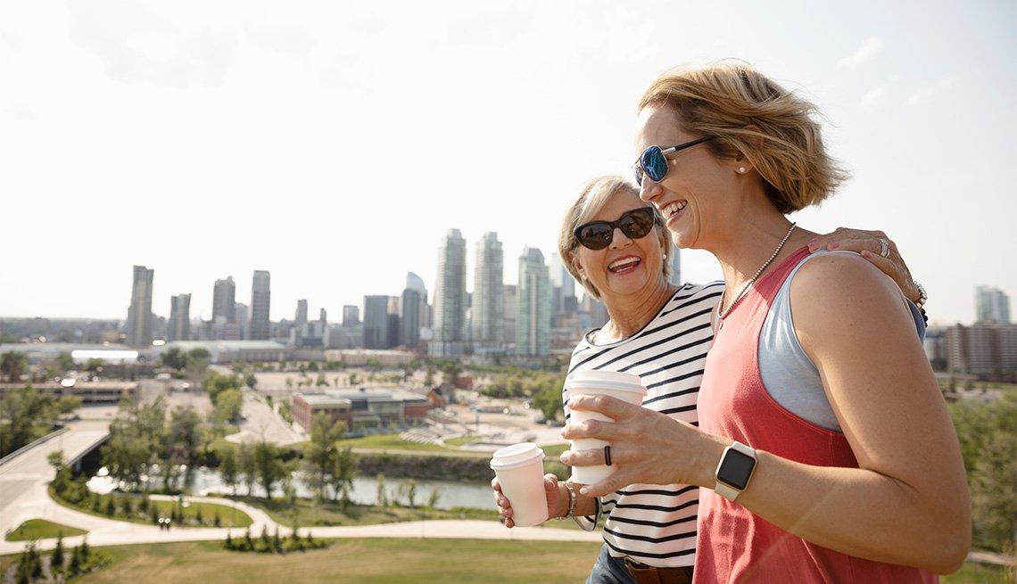 Dos mujeres, madre e hija, sonríen al caminar juntas