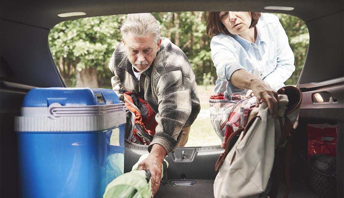 Pareja cargando el auto con suministros para acampar