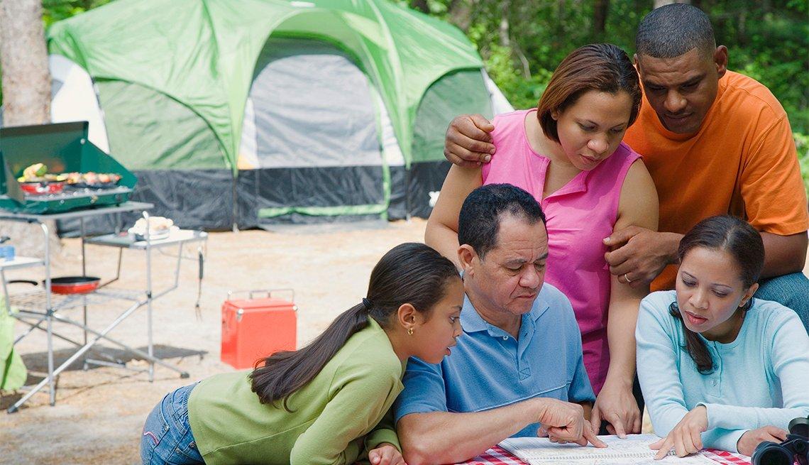 Familia observa un mapa mientras acampa