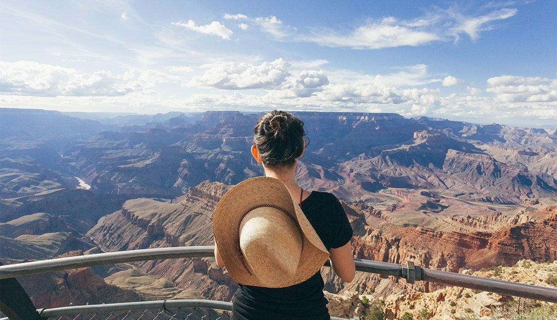 Mujer de pie contra una baranda, observa el Gran Cañón