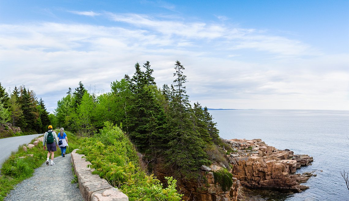 Walkers on path along the coast in Acadia National Park
