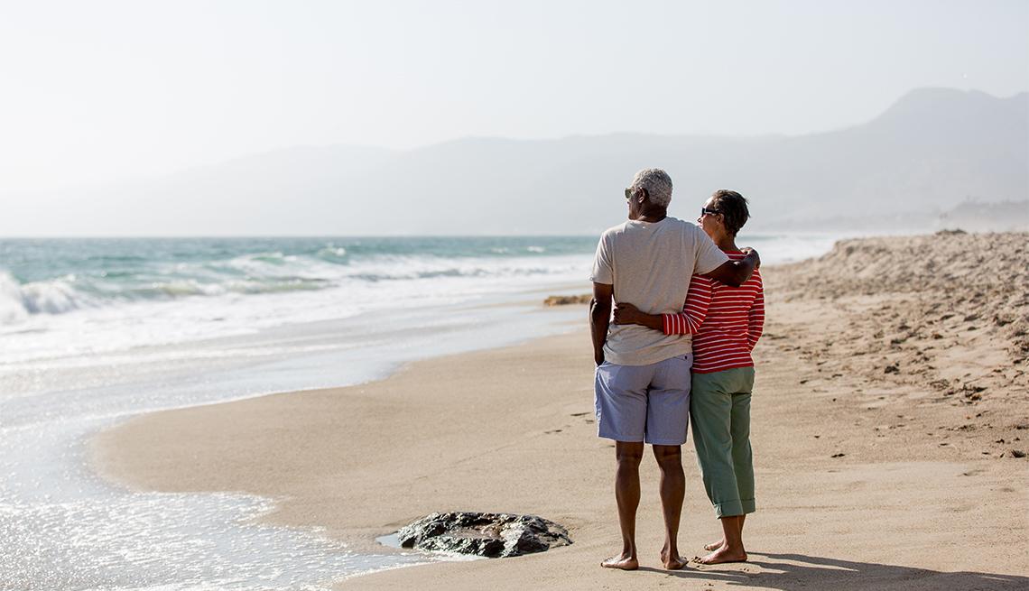 Un hombre y una mujer parados en la playa