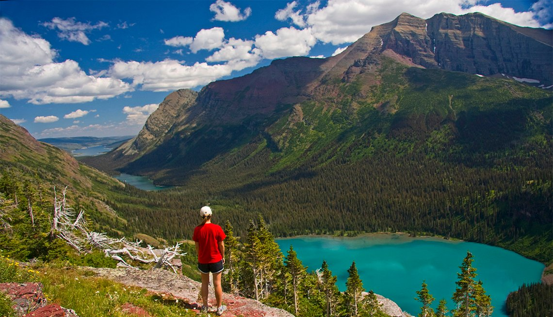 Young woman in red overlooking Grinnell Lake on the Grinnell Glacier Trail in Glacier National Park
