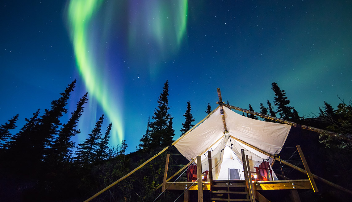 Aurora Borealis glowing green and pink over large canvas luxury camping tent in Alaska