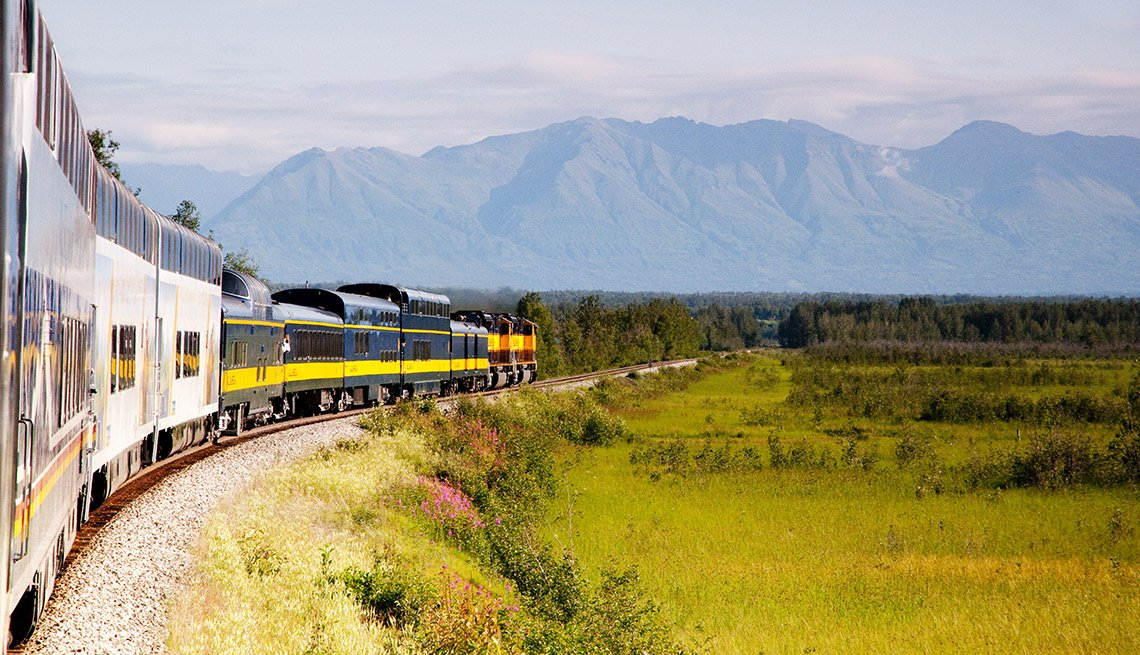 A moving train to Denali is set against a backdrop of an Alaskan landscape with mountains and valleys.