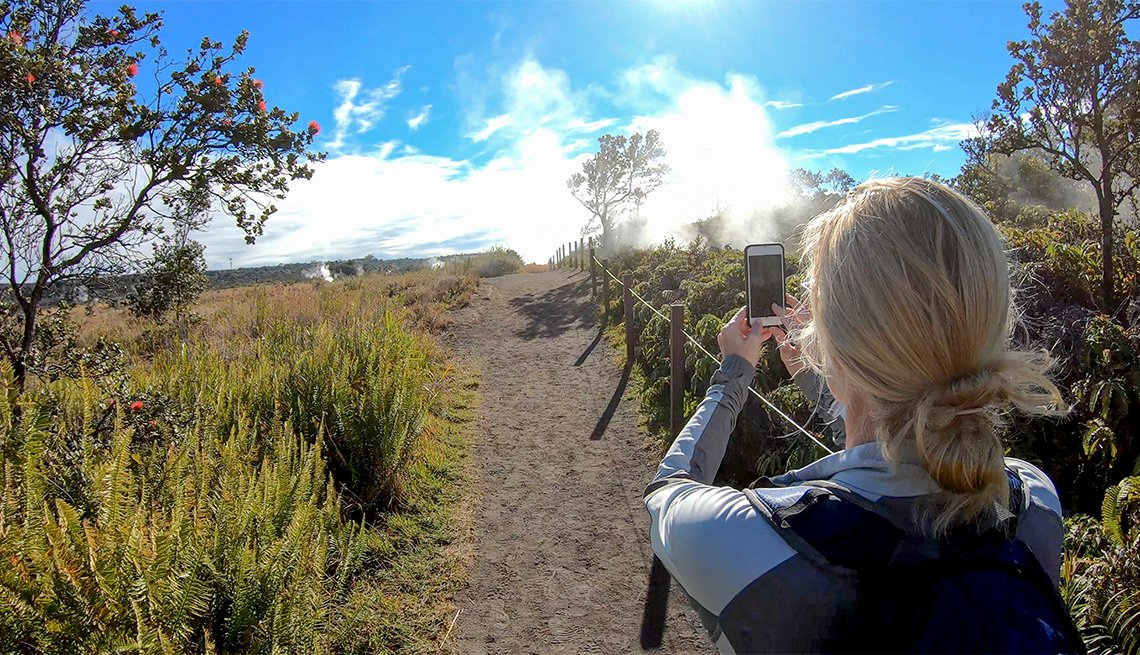 Female hiker takes a photo while on Crater Rim Trail