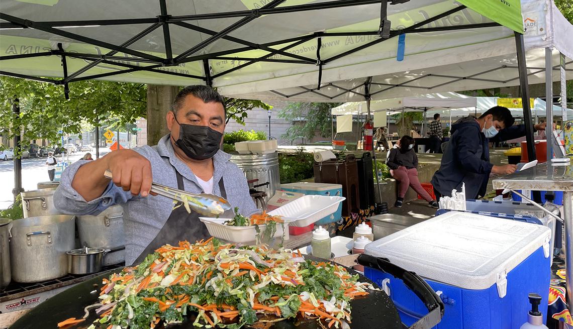 item 2 of Gallery image - Hombre sirve vegetales en un puesto de un mercado agrícola